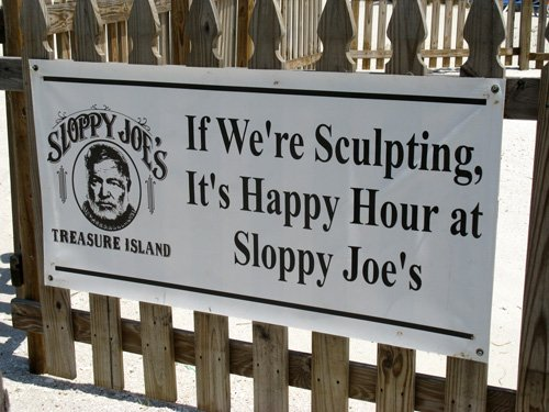 sloppy joes sand sculpture happy hour sign